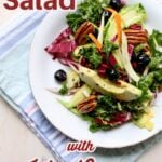 salad of greens blueberries pecans avocado and more on a white plate on a striped blue cloth.