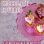 three chocolate strawberries on a pink stand