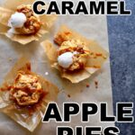 three little caramel apple pies on a gray table on parchment paper with ice cream and caramel sauce drizzled over the top