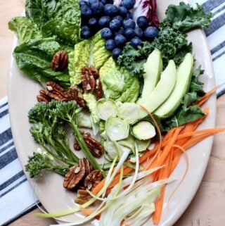 avocado, blueberries, greesn, carrot, fennel, pecans and more on a large white plate sitting on a table