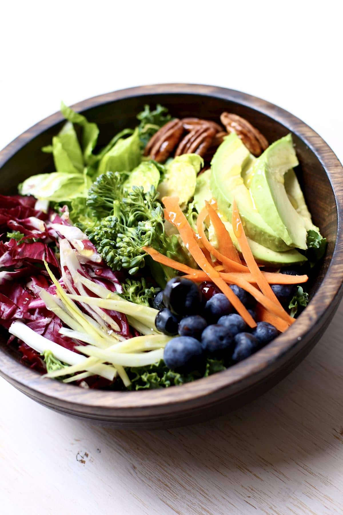 vegetables in a wooden bowl, greens, pecans, avocado, blueberries, pecans and carrots.