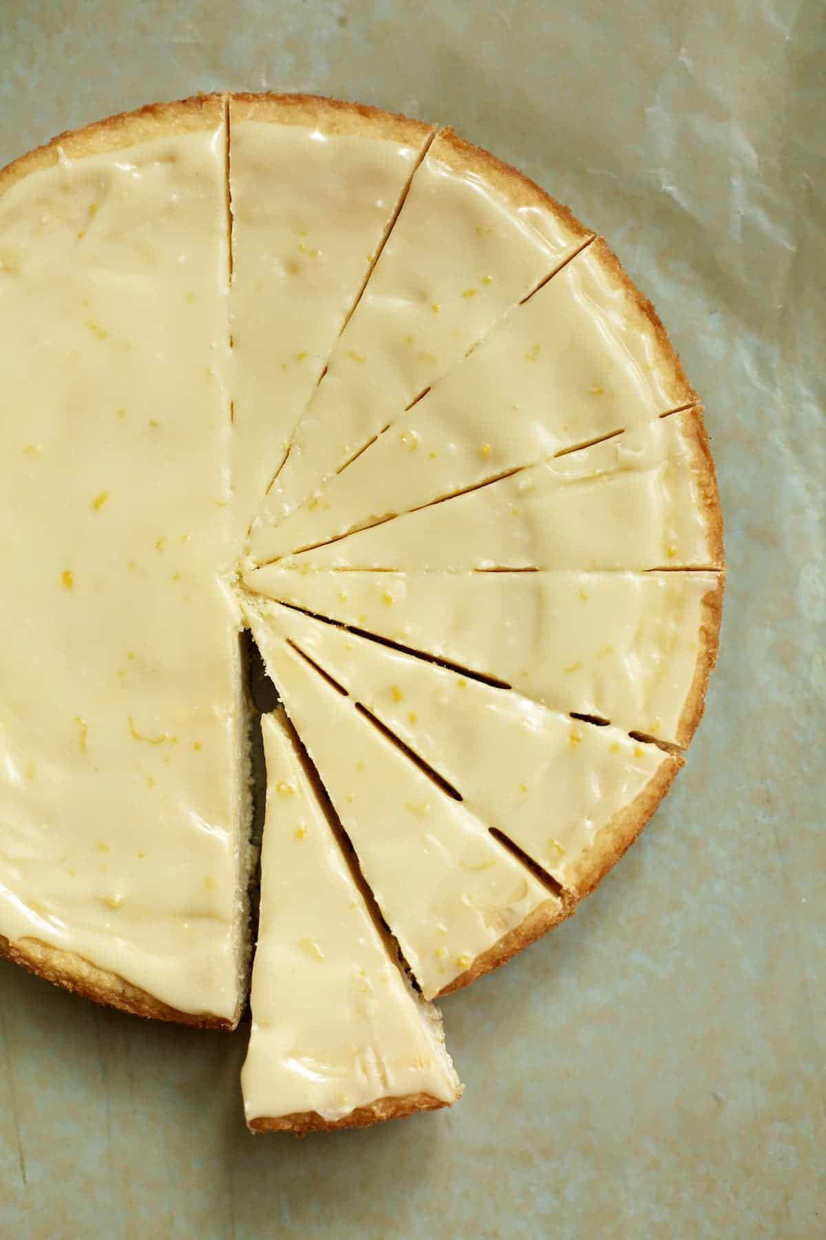 a round of lemon iced shortbread, cut in slices on a piece of parchment paper