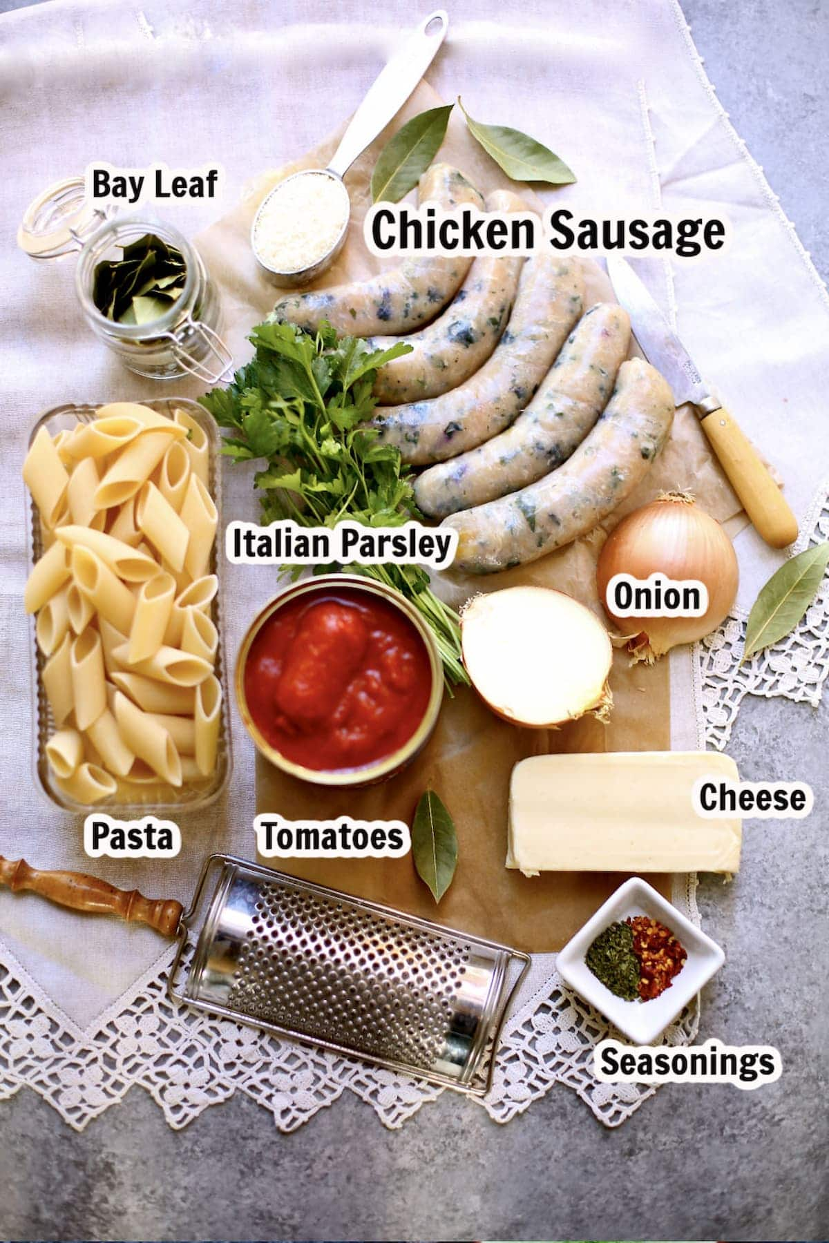 a table of ingredients for baked pasta with sausage, with text overlay saying what eash ingredient is. cheese, tomatos, sausage, pasta, seasonings.