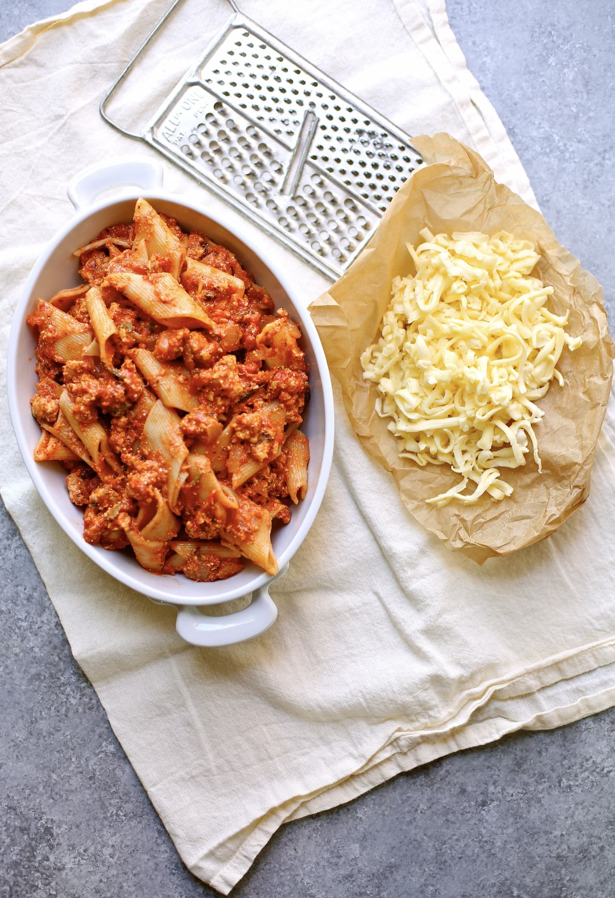 a casserole dish of pasta ready for the oven and some parchment paper with grated cheese next to it, ready to be added to the top and then put in the oven.