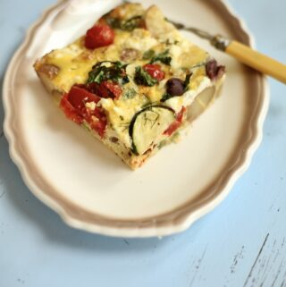 a piece of frittata on a white plate with beige trim with a fork on a blue table.