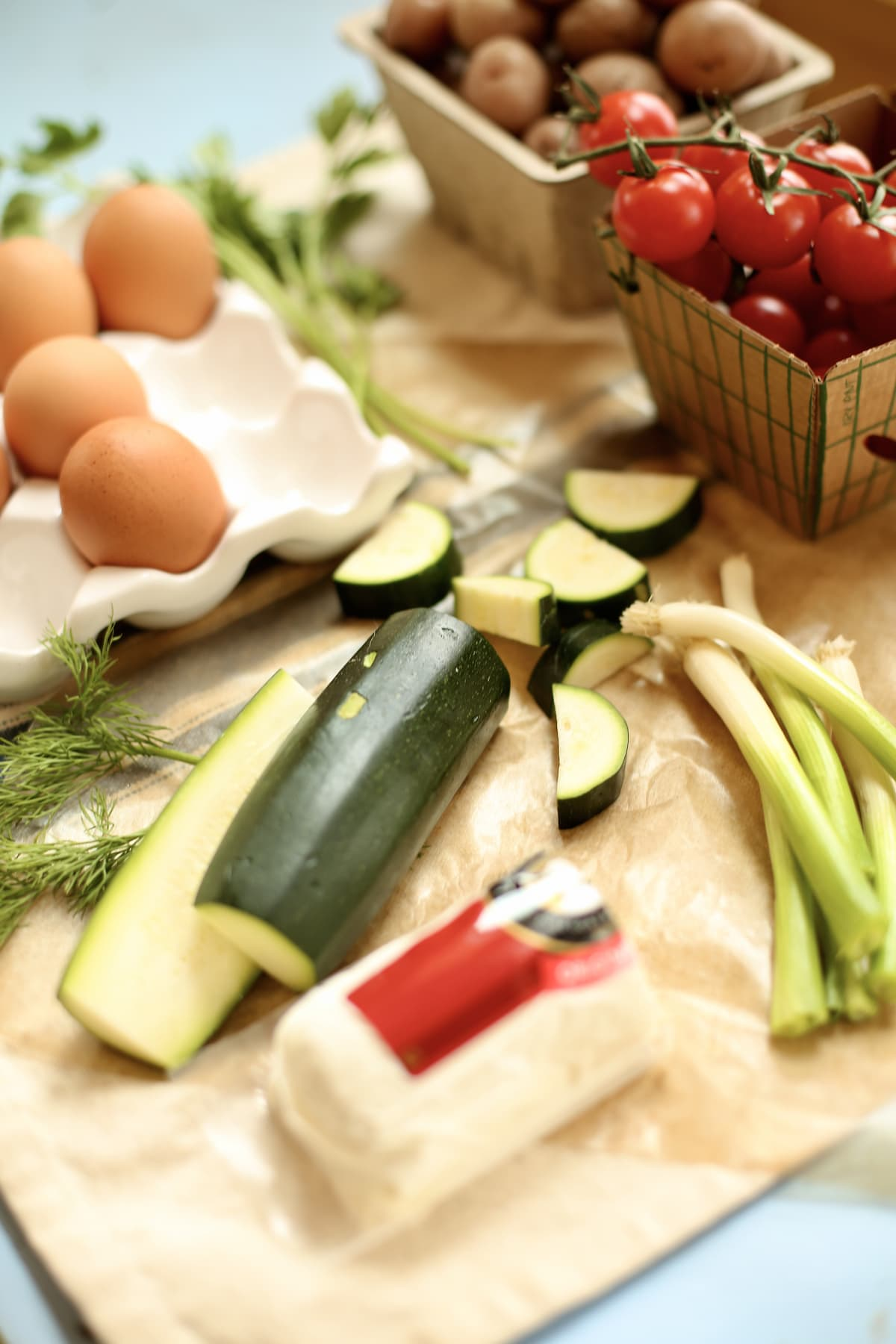 vegetables like zucchini, green onion, goat cheese and eggs on a table being prepped