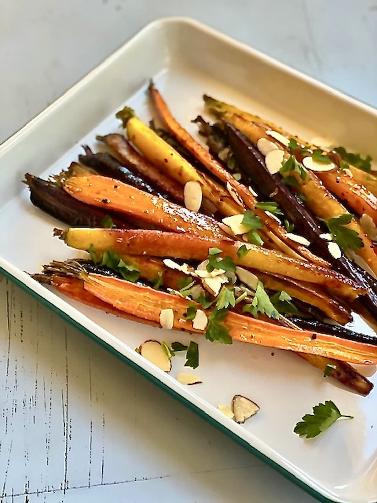 cooked carrots and almonds on a white serving tray