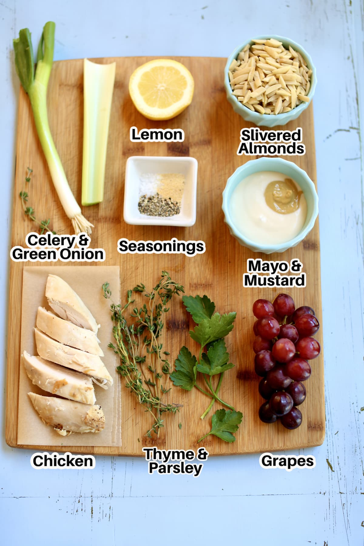 a cutting board of ingredients for chicken salad, rotisserie chicken, fresh herbs, grapes, mayo/mustard, seasonings, celery, lemon, slivered almonds.