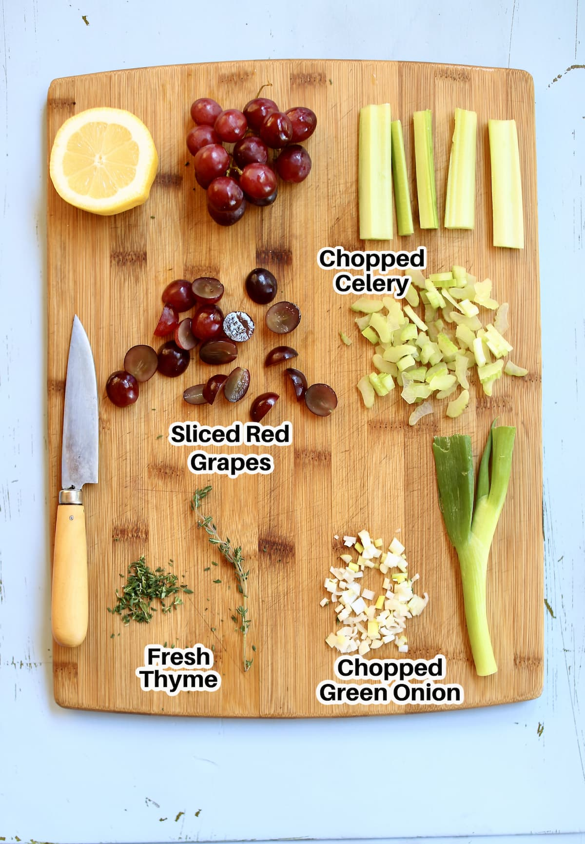 a cutting board with celery, grapes, onion, lemon and thyme for chicken salad