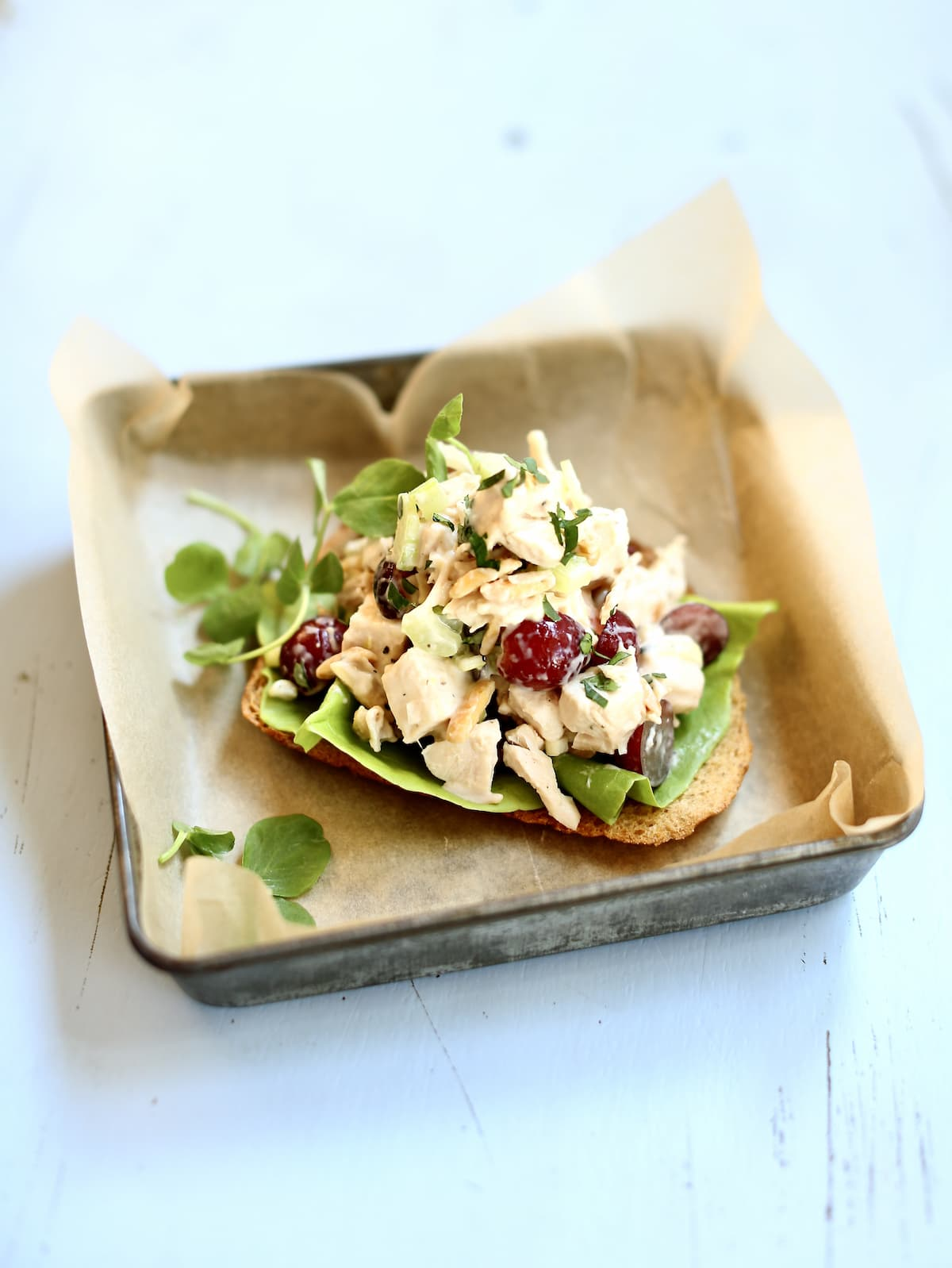 n open-faced chicken salad sandwich in a tin on a blue table
