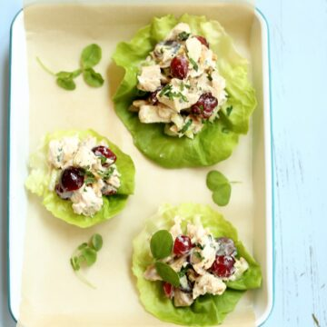 three lettuce leaves with chicken salad on them on a tray with blue background.