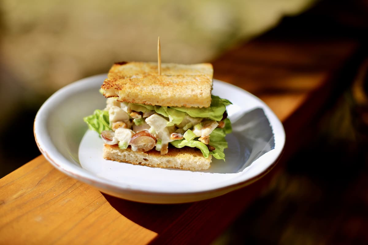 a chicken salad sandwich on a white plate outside