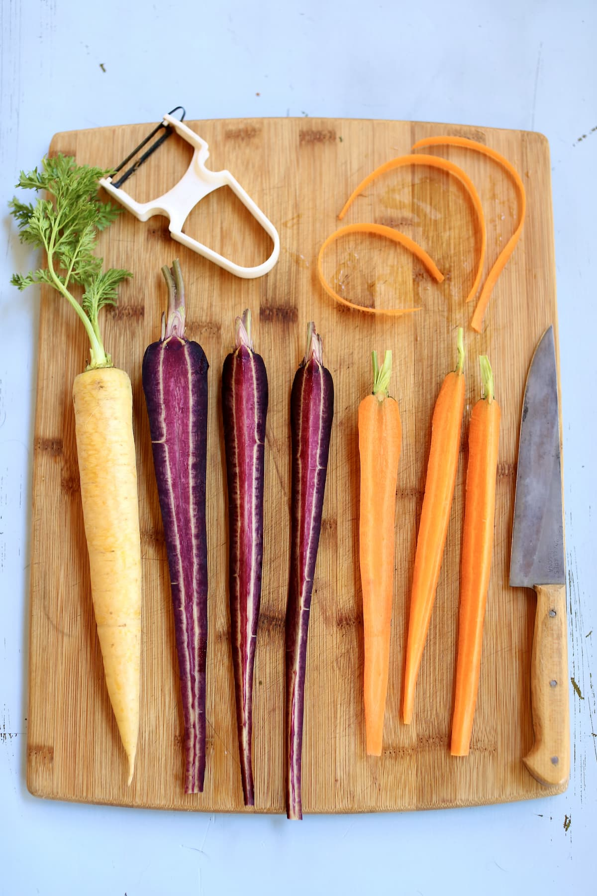 a cutting board with 7 carrots, yellow purple and orange, with a vegetable peeler and a knife.