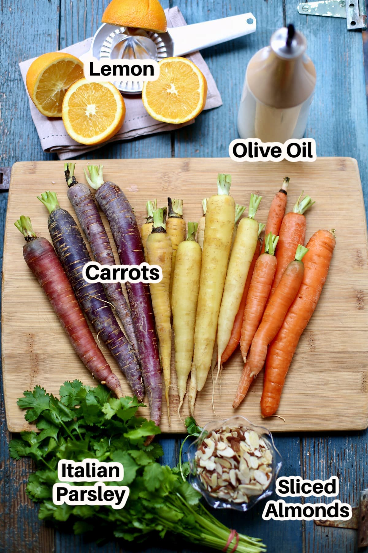 carrots and lemon and olive oil and parsley on a cutting board with blacka nd white text overlay