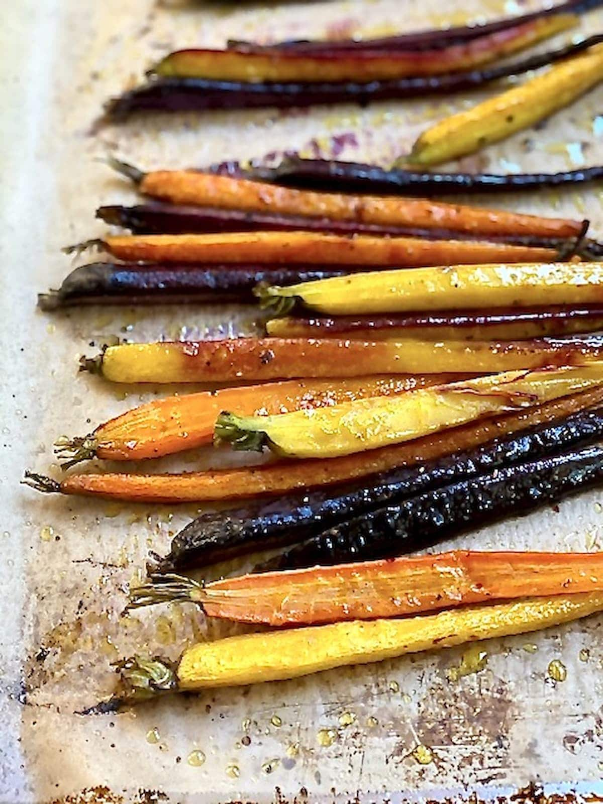 roasted carrots of different colors right out of the oven on a baking sheet.