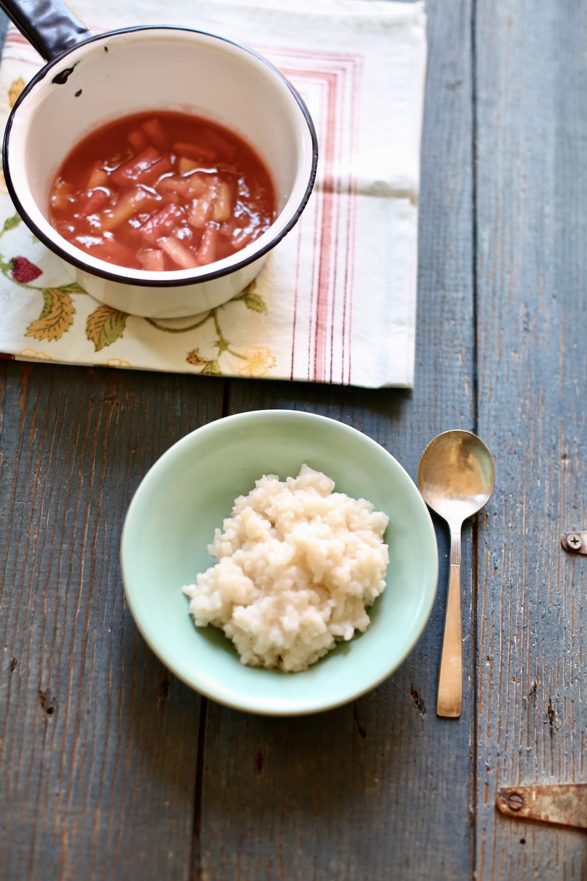 a bowl of rice pudding with a rhubarb sauce on the side on a blue table