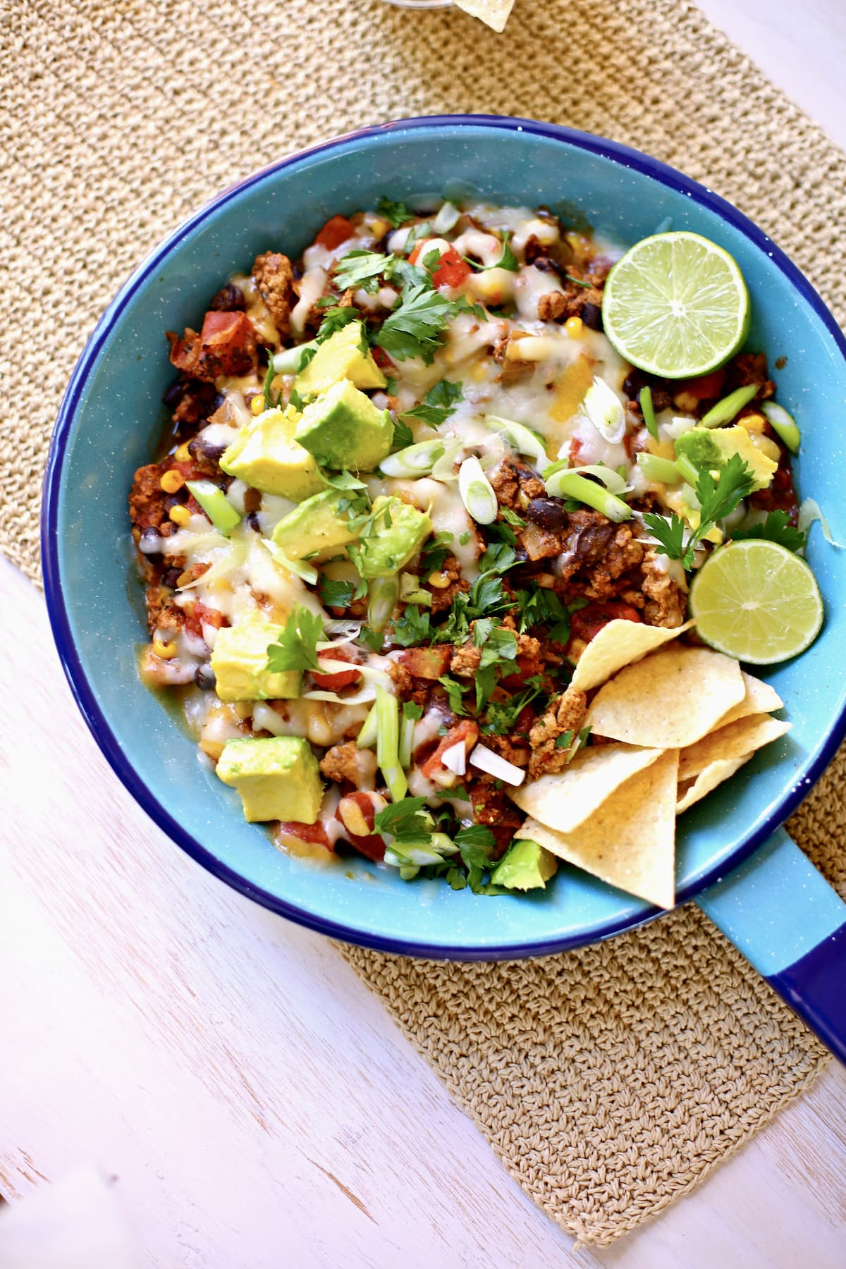 a blue skillet filled with taco emat and cheese and avocados and limes and chips.