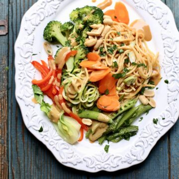 a cold noodle salad with peanut sauce and veggies on a white platter, sitting on a blue wooden table