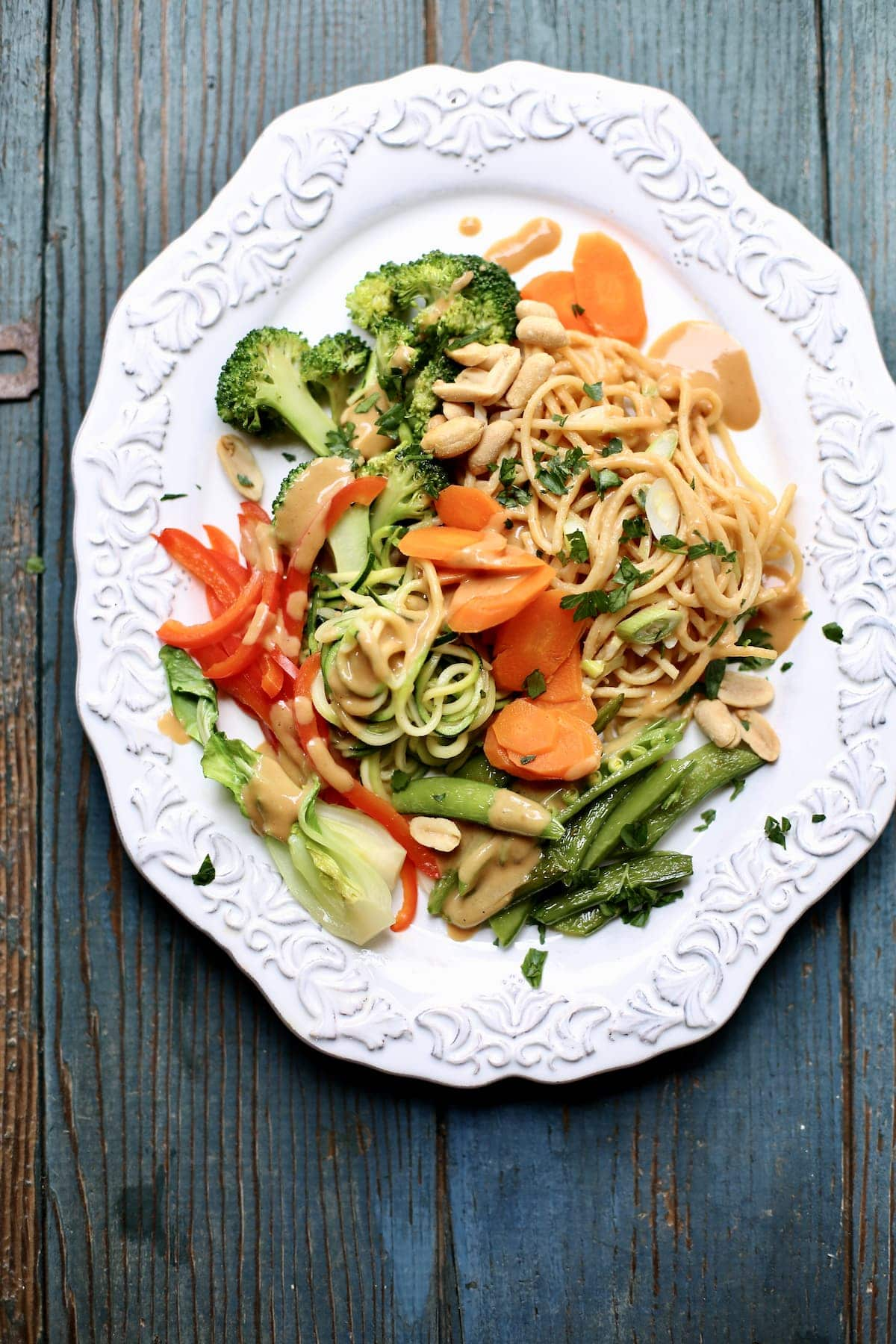 a cold noodle salad with peanut sauce and veggies on a white platter, sitting on a blue wooden table.