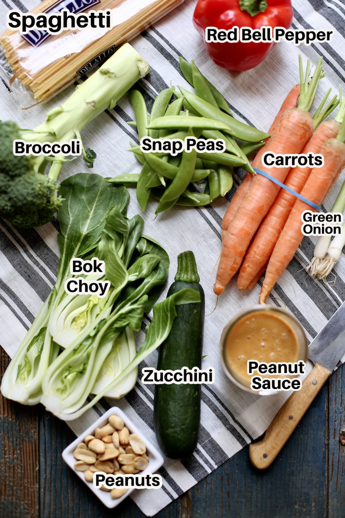a table with striped cloth underneath with a text overlay saying the ingredients: snap peas, carrots, bok choy, zucchini, broccoli, peanut sauce green onion.