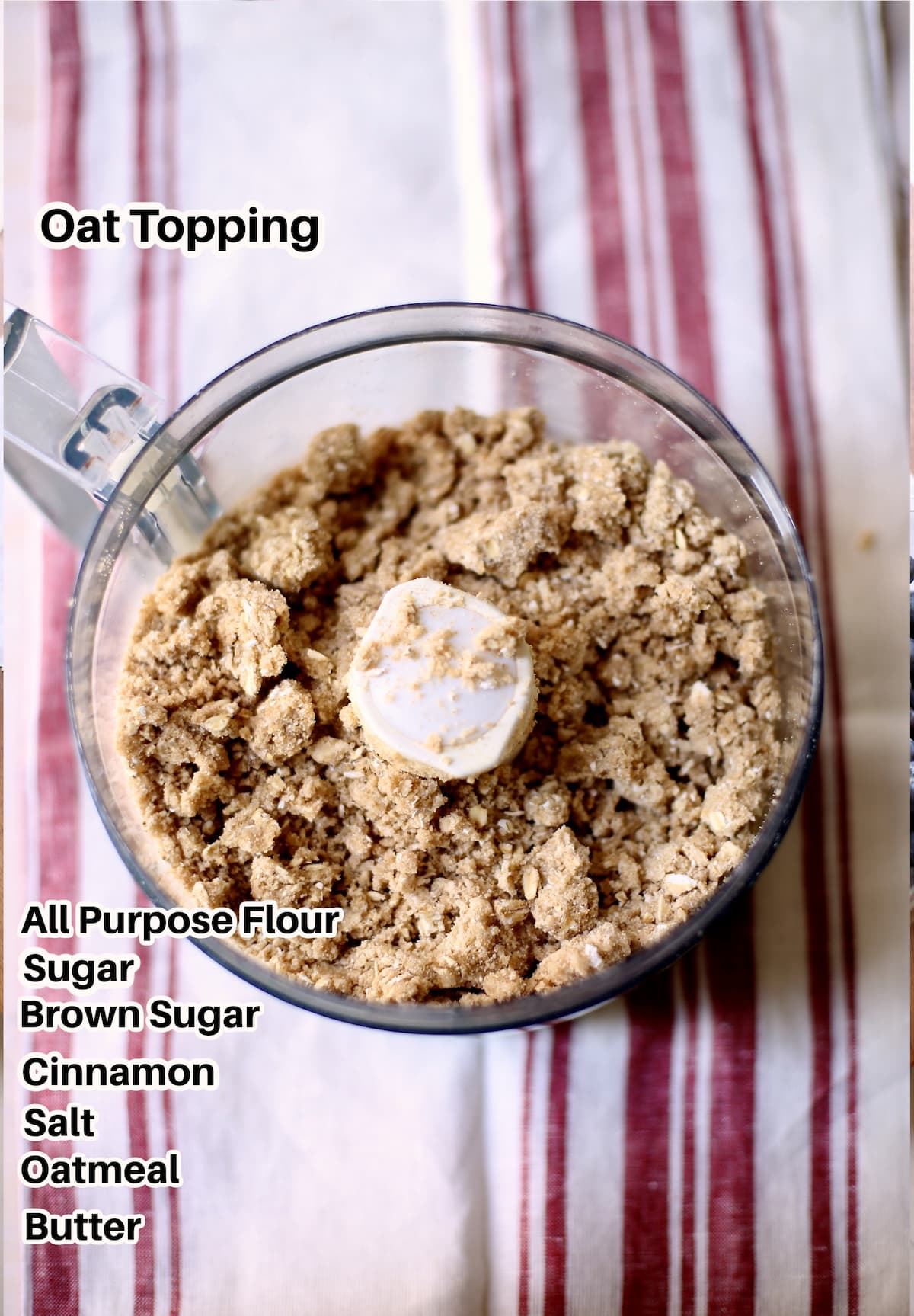 a food processor sits on a striped cloth with text overlay on top saying the ingredients of this oat topping.