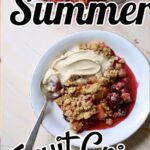 a white dish of summer fruit crisp with vanilla ice cream and a spoon.