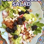 a blue plate with a salad of greens goat cheese and blackberries on a table with text overlay of the recipe name.