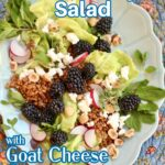 a salad on a long blue plate with text overlay of the recipe name, blackberry salad with goat cheese