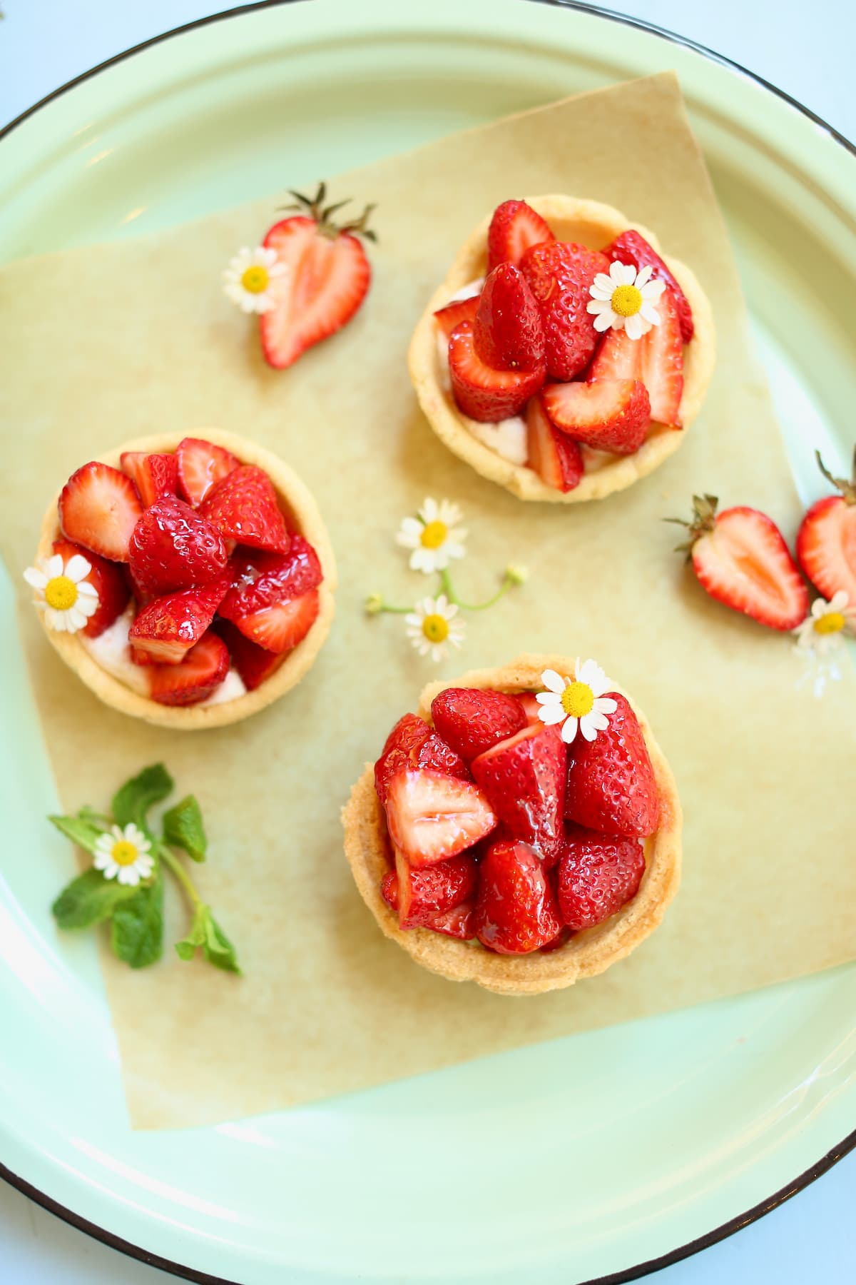 three small strawberry pies on a serving platter with fresh mint and small white flowers as garnish.