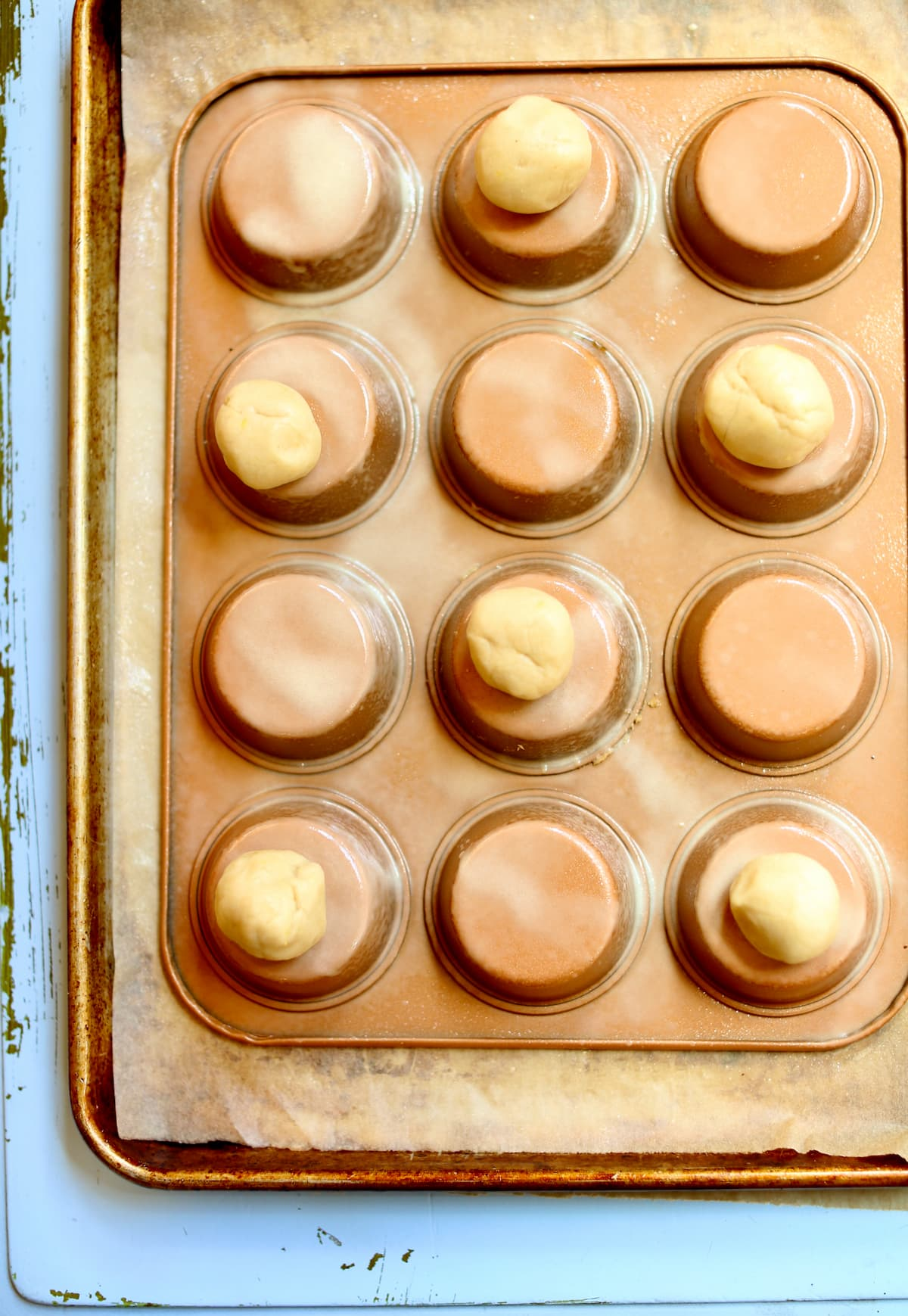 a copper colored muffin tin upsidedown with cookie dough balls on top