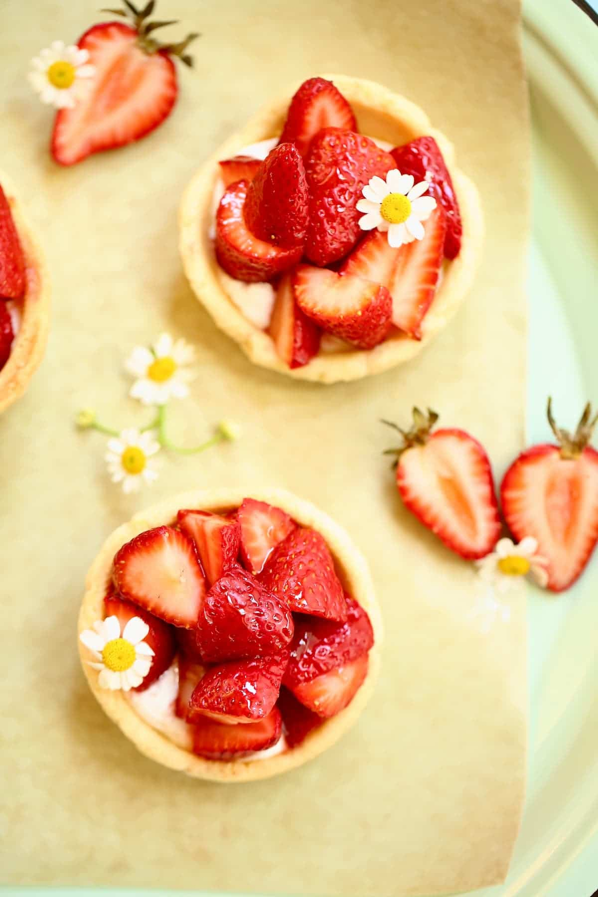 three small strawberry pies with small flowers on a serving tray.