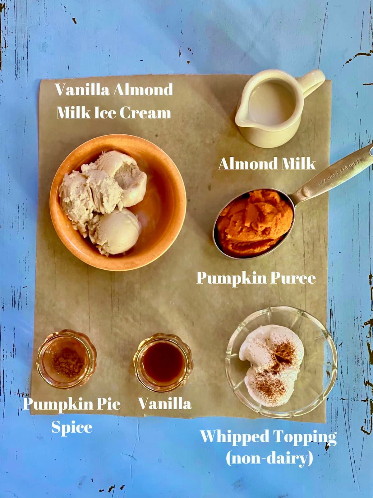 a blue table with ingredients, vanilla ice cream, pumpkin puree, almond milk, pumpkin pie spice, vanilla, with a text overlay saying those ingredient names.