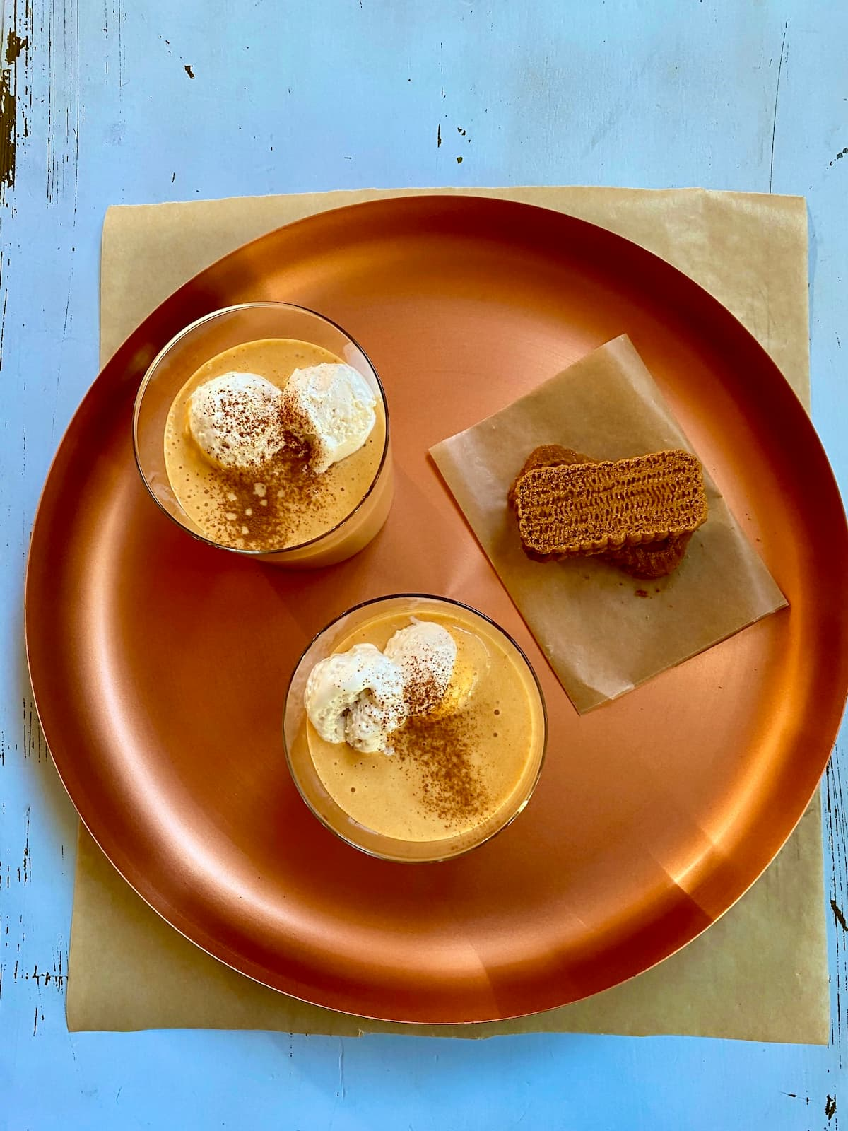 a copper tray with two orange milkshakes and two graham crackers on a blue table.